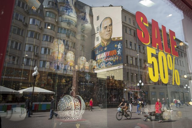 A portrait of Soviet Marshal Georgy Zhukov is reflected in a shop window on a pedestrian street in Moscow, Russia, Thursday, April 30, 2015. Russia will celebrate the 70th anniversary of the Victory in WWII on May 9, 2015. (Photo by Alexander Zemlianichenko/AP Photo)
