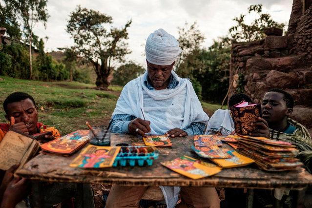 An Ethiopian Orthodox artist paints postcards in Lalibela, Ethiopia, on March 6, 2019. (Photo by Eduardo Soteras/AFP Photo)