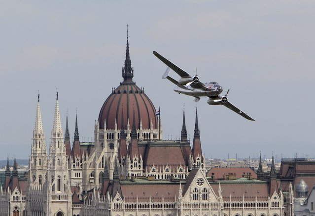 A B-25 airplane performs in front of the Hungarian Parliament during an air show in Budapest, Hungary, May 1, 2015. (Photo by Bernadett Szabo/Reuters)