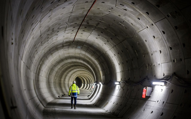 An employees walks on the flat bottom in the round tunnels of the North/South subway line with a pavermachine in Amsterdam, on February 5,2014. Concrete will be poured in three different phases, on which the metro rail can be installed later. (Photo by Lex Van Lieshout/AFP Photo/ANP)