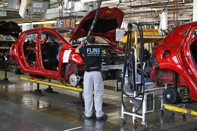 An employee works on the automobile assembly line of a Renault Clio IV at the Renault automobile factory in Flins, west of Paris, France, May 5, 2015. (Photo by Benoit Tessier/Reuters)