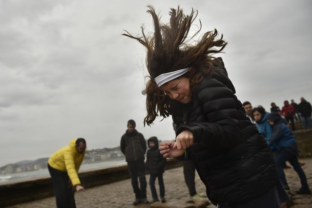 """A young girl protects herself from  the strong wind as she stands by the Basque Monument """"El Peine de los Vientos"""" in San Sebastian northern Spain, Saturday, February 4, 2017. Northern Spain has suffered gale-force winds of up to 120 kilometers per hour (75 miles per hour) over several days. (Photo by Alvaro Barrientos/AP Photo)"""