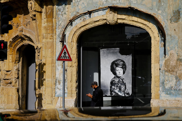 In this November 27, 2018, photo, a man passes in front of Beit Beirut, the nearly 100 year-old house that served as a sniper position during Lebanon's 1975-1990 civil war, on a former Beirut frontline, Lebanon. Nearly 30 years after civil war guns fell silent, dozens of bullet-scarred, shell-pocked buildings are still standing – testimony to a brutal conflict that raged for 15 years and took the lives of 150,000 people. (Photo by Hassan Ammar/AP Photo)
