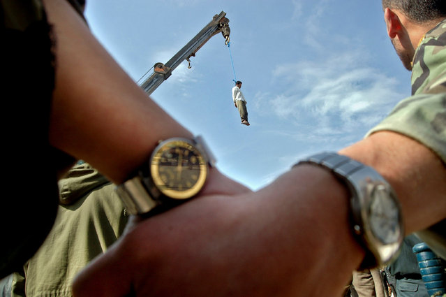 Serial killer Mohammad Bijeh, who was convicted of kidnapping and murdering 21 people, most of them children, is hauled into the air hanging from the arm of a crane after his execution on 16 March, 2005. Bijeh, branded 'the vampire of the desert' in Iran, was lashed 100 times and hanged before thousands of spectators. (Photo by Hossein Fatemi/Reuters/Panos Pictures/Courtesy of World Press Photo Foundation)