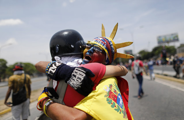 An anti-government protester dressed as Lady Liberty, wearing the colors of Venezuela's flag, hugs a fellow protester during a demonstration near La Carlota airbase in Caracas, Venezuela, Wednesday, May 1, 2019. (Photo by Ariana Cubillos/AP Photo)