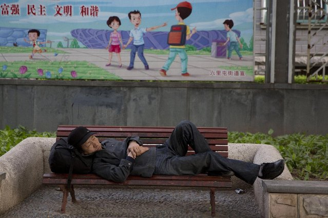 """A man sleeps on a bench near government slogans """"Prosperous, democratic, civilized and harmonious, top left"""", on a street in Beijing, Tuesday, May 5, 2015. Government propaganda are a common sight in the Chinese capital, a remainder it is also the political center of China. (Photo by Ng Han Guan/AP Photo)"""