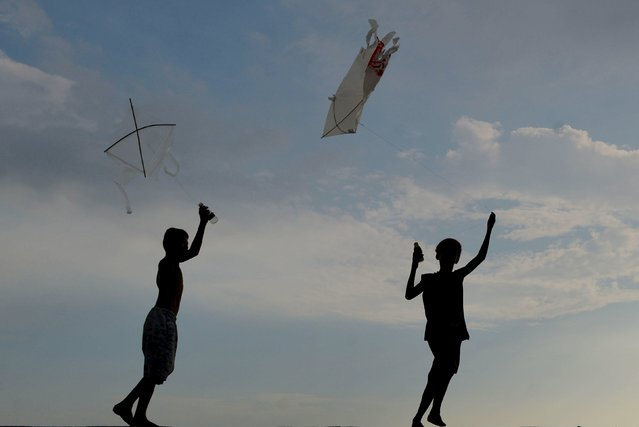 Boys are silhouetted as they fly their kites during summer school break in Navotas, Metro Manila May 6, 2015. Schools are closed for two months during summer break in the Philippines. (Photo by Ezra Acayan/Reuters)