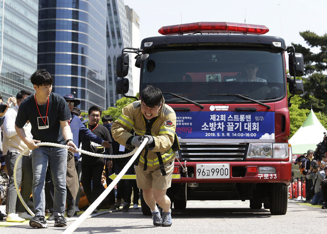 Firefighter Yeom Jung-phil pulls a fire truck by a rope during the Safe Seoul Festival in Seoul, South Korea, Thursday, May 9, 2019. The festival will be held to promote safety awareness and educational program from May 9 to May 12. (Photo by Ahn Young-joonAP Photo)