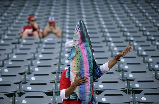 Dee Dee Deleon, of San Diego, holds a trout pillow autographed by Los Angeles Angels' Mike Trout before the Angels' baseball game against the Colorado Rockies, Wednesday, May 13, 2015, in Anaheim, Calif. (Photo by Jae C. Hong/AP Photo)
