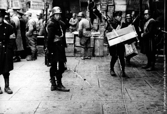 1944: Empty cases, which some days ago were packed with millions of newly printed currency notes, are used to build barricades to control a possible rush by refugees anxious to obtain their promised payments
