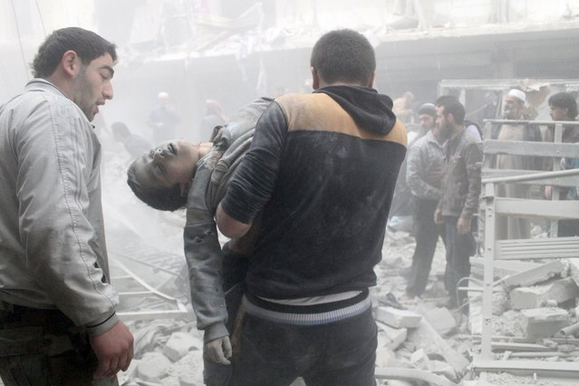 A Syrian man evacuates a child found in the rubble of a residential building reportedly hit by an explosives-filled barrel dropped by a government forces helicopter on March 18, 2014 in Aleppo. (Photo by Khaled Khatib/AFP Photo)