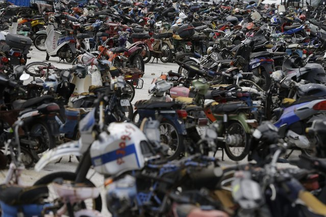 Hundreds of motorcycles are parked at the Public Property Management Organization (ODDY) during an auction in western Athens on Tuesday, May 19, 2015. The ODDY frequently auctions state and confiscated vehicles with hundreds of people trying to buy them at low prices. (Photo by Thanassis Stavrakis/AP Photo)