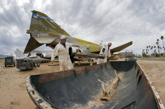 Phil Kovaric and Dennis Varney remove the missile rails from an F-4 Phantom slated for destruction at the 309th Aerospace Maintenance and Regeneration Group boneyard in Tucson, Ariz. on Thursday, May 21, 2015. The 309th is the United States Air Force's aircraft and missile storage and maintenance facility and provides long and short-term aircraft storage, parts reclamation and disposal. (Photo by Matt York/AP Photo)