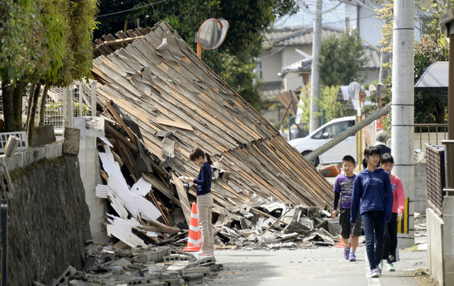 Children walk past a house collapsed by a magnitude-6.5 earthquake in Mashiki, Kumamoto prefecture, southern Japan, Friday, April 15, 2016. The powerful earthquake struck Thursday night, knocking down houses and buckling roads. (Photo by Koji Harada/Kyodo News via AP Photo)