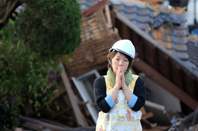 A residents stand in front of damaged house in Mashiki, Kumamoto prefecture, southern Japan Saturday, April 16, 2016. A powerful earthquake struck southern Japan early Saturday, barely 24 hours after a smaller quake hit the same region. (Photo by Naoya Osato/Kyodo News via AP Photo)