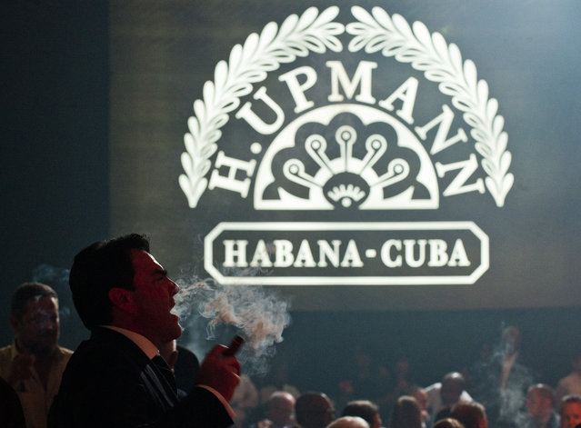 People smoke cigars during a banquet at the XVI Havana Cigar Festival in the Cuban capital on February 28, 2014. The production of Cuban cigars experienced an eight percent growth in 2013 adding 447 million dollars to the Cuban economy. (Photo by Yamil Lage/AFP Photo)