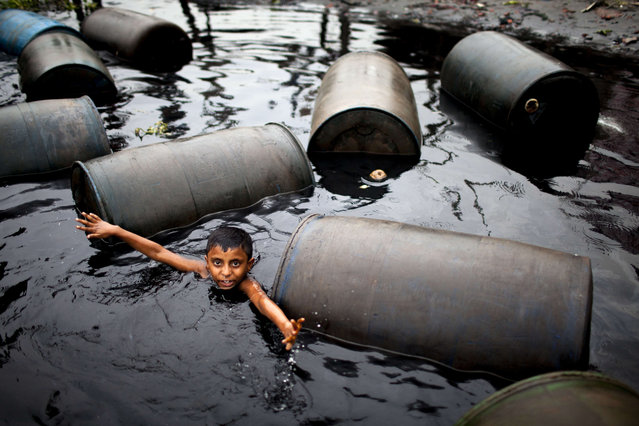 Boy swim in the toxic water full of discarded oil tanks in the River Buriganga, Dhaka, Bangladesh on May 29, 2017. The river water is extremely polluted. Sewage from the city, oil spills from boats and chemicals from industry have all led to pollution of the water. (Photo by K.M. Asad/LightRocket via Getty Images)