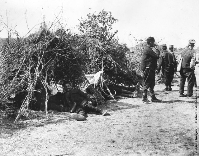 1915:  Serbian allied soldiers in twig tents at a camp in Serbia, during the First World War