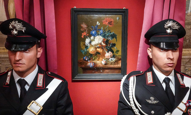 """Policemen stand guard next to the veiled painting """"Vase of Flowers"""" by Dutch artist Jan van Huysum during its return ceremony at the Pitti Palace, part of the Uffizi Gallery in Florence, Italy, 19 July 2019. The artwork was stolen by Nazi troops during World War II. (Photo by Claudio Fusi/Rex Features/Shutterstock)"""