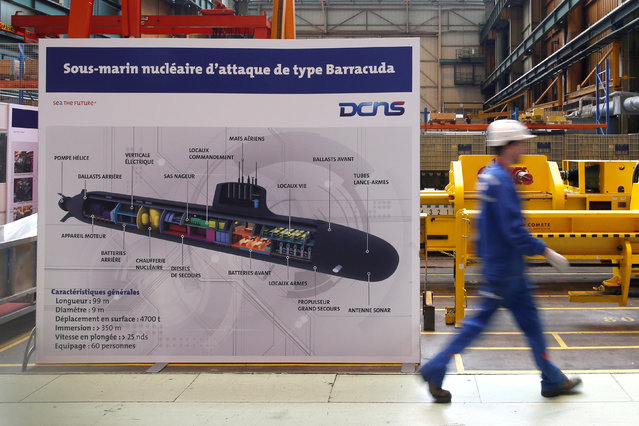 An employee walks past a poster showing a Barracuda submarine at the industrial site of the naval defence company and shipbuilder DCNS in La Montagne near Nantes, France, April 26, 2016. (Photo by Stephane Mahe/Reuters)