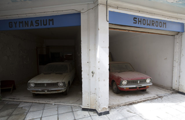 Cars sit abandoned in a former shopping centre in the United Nations buffer zone in central Nicosia March 12, 2014. The cars were imported from Japan to be sold at a Toyota dealership. They were stored here during the 1974 conflict and have not been moved since. (Photo by Neil Hall/Reuters)