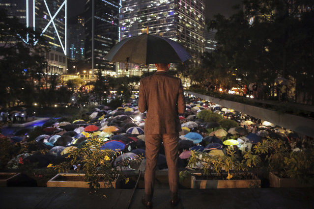 A man holding an umbrella looks at people with umbrellas gathered at Chater Garden to give support to the recent protests against the extradition bill, at the financial district in Hong Kong, Thursday, August 1, 2019. (Photo by Elson Li/HK01 via AP Photo)