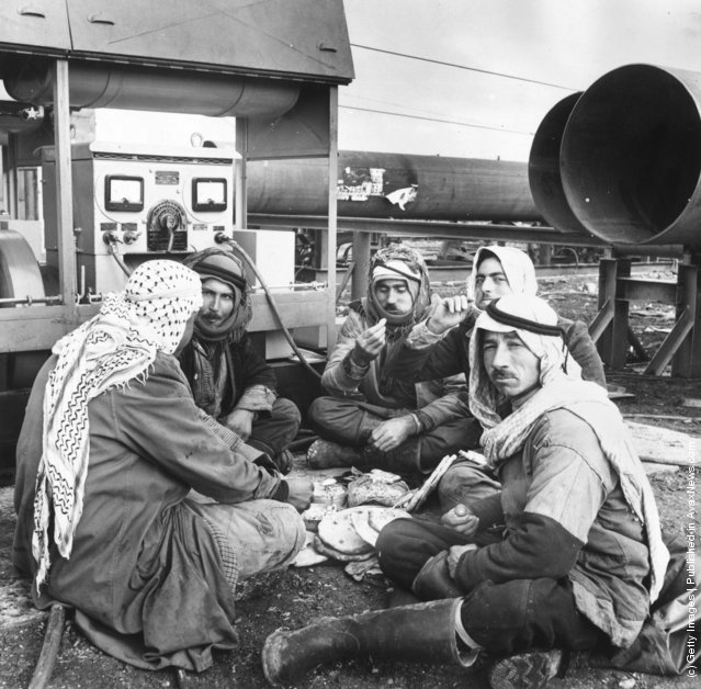 1952: A group of Bedouin Arab men, who are working on the laying of a 560 mile long pipeline from Kirkuk in north Iraq to Bania on the Syrian coast for the Iraq Petroleum Company, having their lunch surrounded by sections of the pipe