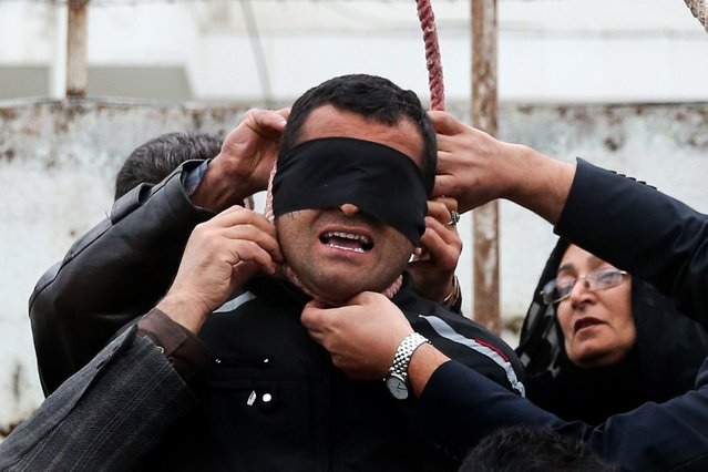 The mother (R) of Abdolah Hosseinzadeh, who was murdered in 2007, removes the noose with the help of her husband from around the neck of Balal, who killed her son, during the execution ceremony in the northern city of Nowshahr on April 15, 2014, sparing the life of her son's convicted murderer. The dramatic events followed a rare public campaign to save the life of Balal, who at 19 killed another young man, Abdollah Hosseinzadeh, in a street fight with a knife back in 2007. (Photo by Araash Khamooshi/AFP Photo/ISNA)