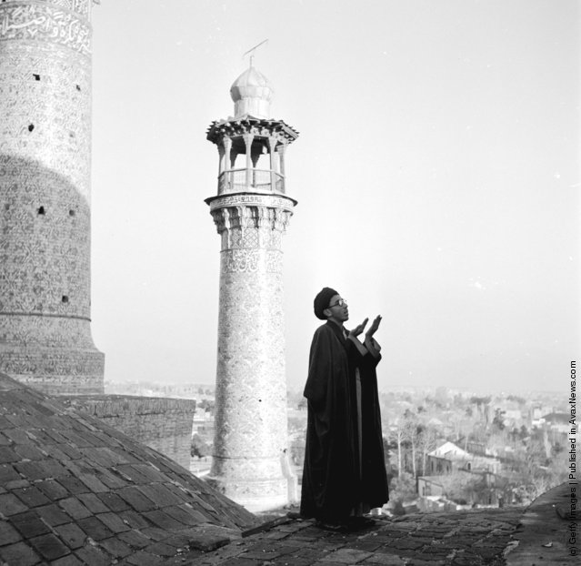 1952:  Standing on a rooftop a muezzin is calling the faithful to prayer. Behind him rises a minaret
