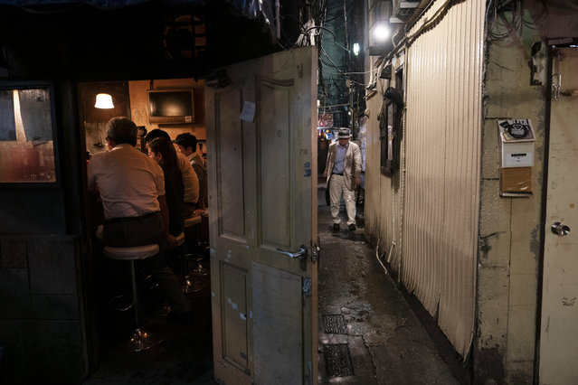 A man, right, makes his way through a narrow passageway between two buildings at the Golden Gai in the Shinjuku district of Tokyo, July 17, 2019. (Photo by Jae C. Hong/AP Photo)