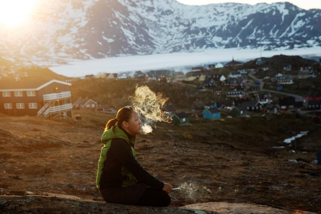 A young girl sits on a stone and smokes in the late evening sunshine above the town of Tasiilaq, Greenland, June 18, 2018. (Photo by Lucas Jackson/Reuters)
