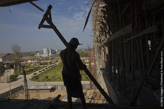 Burmese workers carry wood at a construction site for a new 140 room hotel