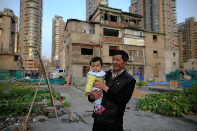 Yueyue is held by her grandfather in an empty area outside their house at Guangfuli neighbourhood, in Shanghai, China, April 1, 2016. (Photo by Aly Song/Reuters)