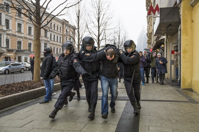 Police officers detain a man in the main street in Moscow, Russia, Sunday, April 2, 2017. (Photo by Pavel Golovkin/AP Photo)