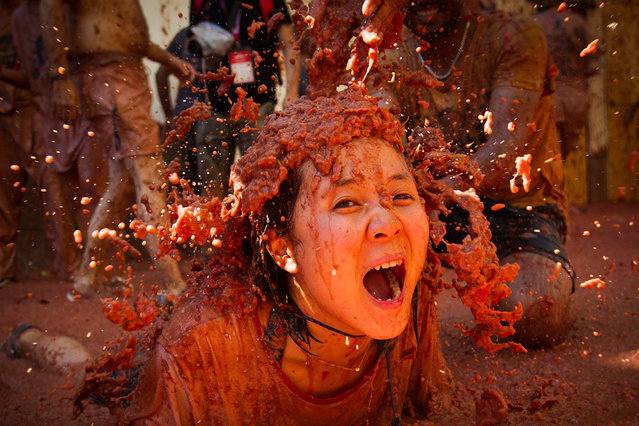 "A reveller covered in tomato pulp participates in the annual ""Tomatina"" festival in the eastern town of Bunol, on August 28, 2019. The iconic fiesta, which is billed at ""the world's biggest food fight"" has become a major draw for foreigners, in particular from Britain, Japan and the United States. (Photo by Jaime Reina/AFP Photo)"