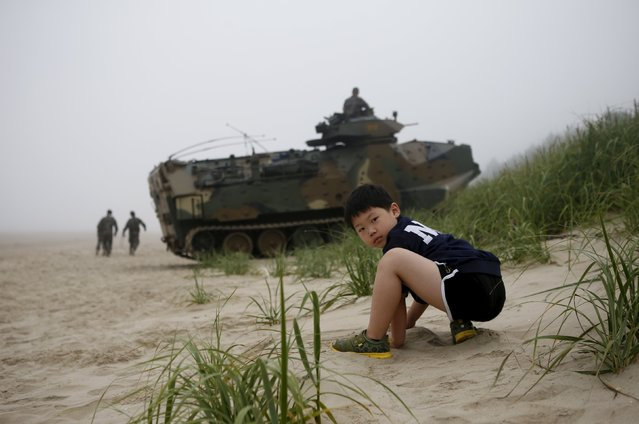 A boy plays with sand next to amphibious assault vehicles of the South Korean Marine Corps during a landing operation drill in Taean, South Korea, June 29, 2015. (Photo by Kim Hong-Ji/Reuters)