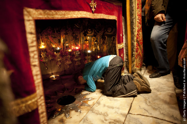 A Christian boy prays at the Grotto in the Church of the Nativity