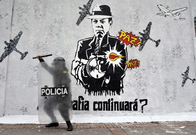A police officer stands guard next to a grafffiti of Colombian President Juan Manuel Santos during a May Day protest on May 1, 2014, in Bogota, Colombia. (Photo by Guillermo Legaria/AFP Photo)