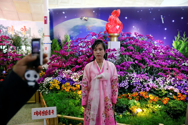 A woman wearing traditional clothes poses for a photo during the flower exhibition marking the 105th birth anniversary of the country's founding father, Kim Il Sung in Pyongyang, North Korea April 16, 2017. (Photo by Damir Sagolj/Reuters)