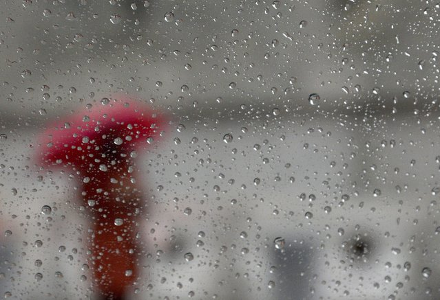 A woman stands in the rain near the United Nations headquarters, in New York City, New York, USA, 30 April 2014. Heavy rain across the US east coast has caused road and air traffic delays across the region, according to reports. (Photo by Andrew Gombert/EPA)