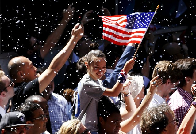 A fan holds an American flag as paper falls from buildings above during the ticker tape parade for the U.S. women's soccer team to celebrate their World Cup final win over Japan, in New York, July 10, 2015. (Photo by Mike Segar/Reuters)
