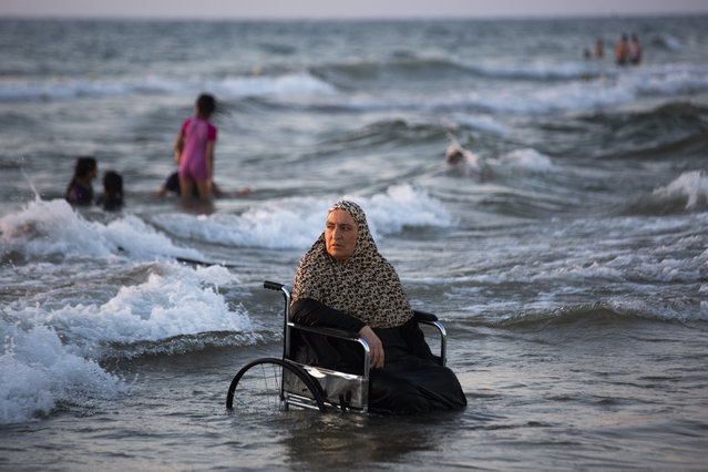 A Palestinians woman from the West Bank town of Qalqilya sits in wheelchair in the mediterranean sea during the Eid Al Adha festival in Tel Aviv's beach, Israel, Wednesday, August 14, 2019. Palestinians visited Tel Aviv and other places in Israel after Israel granted travel permits to West Bank Palestinians. (Photo by Oded Balilty/AP Photo)