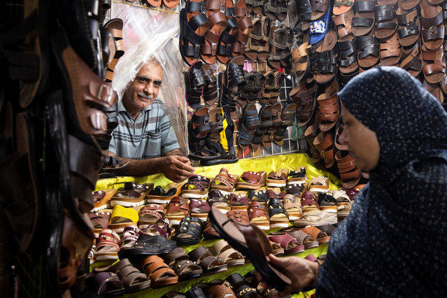 An Iranian woman buys shoes at a shoes store in a local bazaar at Bandar Abbas, Iran on August 22, 2019. (Photo by Nazanin Tabatabaee/WANA (West Asia News Agency) via Reuters)