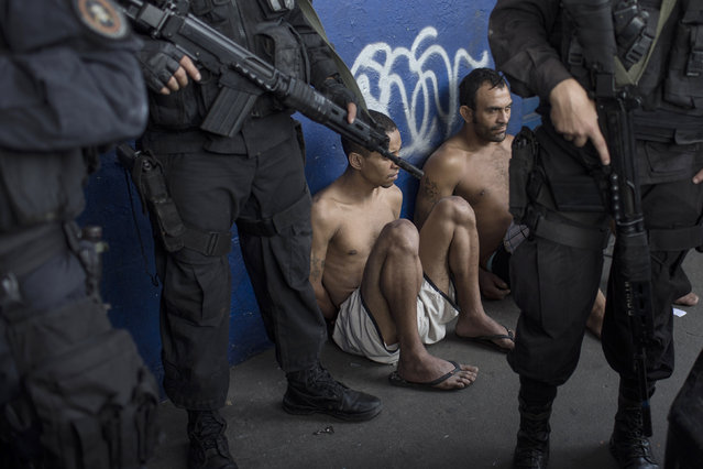 Suspects sit with their hands behind their backs after their arrest during a police operation in the Nova Holanda slum, part of the Complexo da Mare, in Rio de Janeiro, Tuesday, June 25, 2013. The police operation aimed to capture an alleged looter, who according to police killed an officer after a peaceful protest Monday night. At least seven people died and two suspects were captured during Tuesday's operation, according to police. (Photo by Felipe Dana/AP Photo)