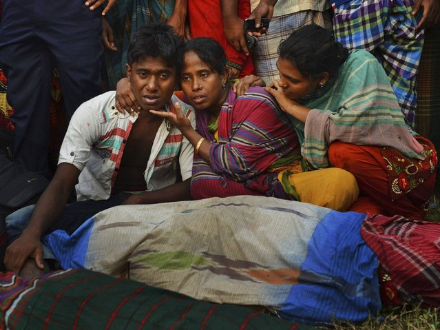 Bangladeshi relatives wail near bodies of victims on the banks of the River Meghna after a ferry capsized and sank after being hit by a storm in Munshiganj district. (Photo by Sony Ramany/AP Photo)