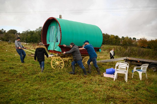 People manoeuvre a traditional caravan onto a trailer at the biannual Stow Horse Fair in the town of Stow-on-the-Wold, England on October 24, 2019. The Stow Horse Fair has attracted Gypsy and Traveller people from all over the country to the Cotswold town every May and October since 1476. (Photo by Oli Scarff/AFP Photo)