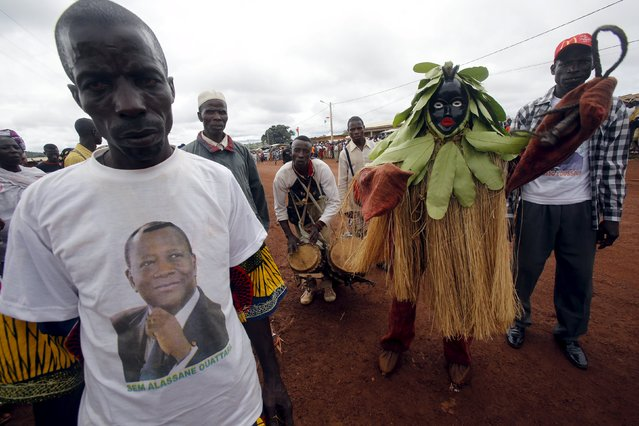 A supporter of Ivory Coast's President Alassane Ouattara wearing a t-shirt bearing his image, waits for his arrival as he makes his state visit at the Ouaninou village, in Touba, in northwestern Ivory Coast July 22, 2015. (Photo by Luc Gnago/Reuters)