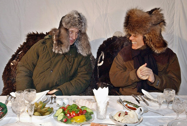 In this February 3, 2003 file photo Russian President Vladimir Putin, left, shares a word with former Italian Prime Minister Silvio Berlusconi during their informal outdoor dinner at the Zavidovo Putin's residence, about 120 km (75 miles) northwest of Moscow. A boast by Berlusconi that his old friend Putin had offered to make him economy minister made headlines around the world this week. (Photo by ITAR-TASS, Presidential Press Service via AP Photo)