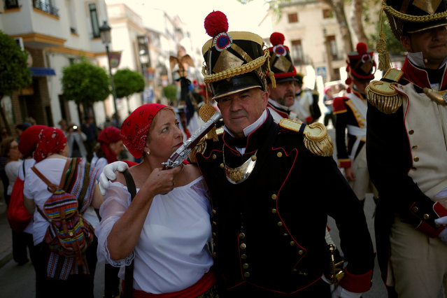"""Members of a historical battle re-enactment group, dressed as bandits and the French army, joke before participating in a Spanish Independence War battle re-enactment during the fifth edition of """"Ronda Romantica"""" (Romantic Ronda) in Ronda, southern Spain, May 27, 2017. (Photo by Jon Nazca/Reuters)"""