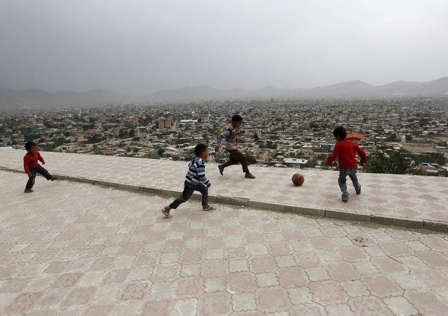 Afghan boys play soccer on a hilltop overlooking Kabul, Afghanistan April 26, 2015. (Photo by Mohammad Ismail/Reuters)